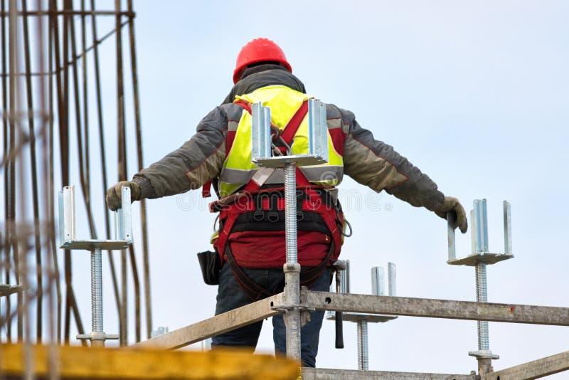 Ο εργαζόμενος με τη ζώνη ασφάλειας αναρριχείται στο εργοτάξιο οικοδομής στοκ φωτογραφία