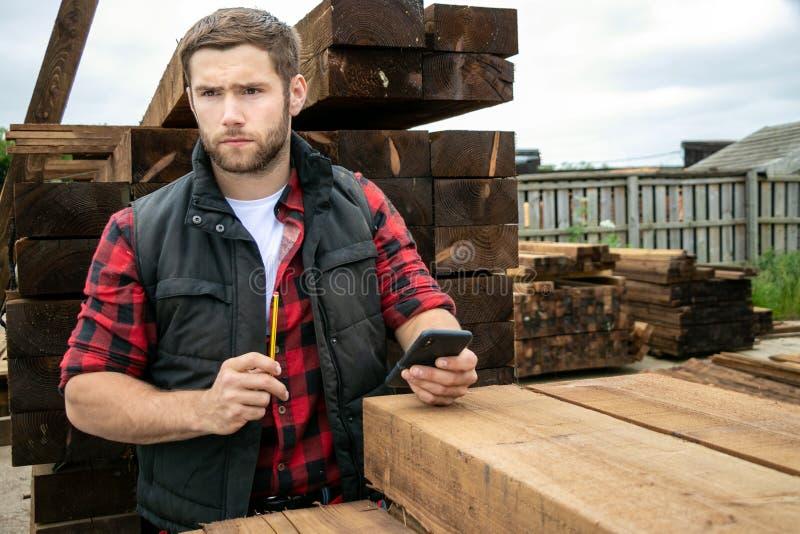 Ο εργαζόμενος ναυπηγείων ξυλείας, ξυλουργός στο ξύλινο ναυπηγείο μετρά τον κατάλογο με την κινητή συσκευή στοκ φωτογραφία με δικαίωμα ελεύθερης χρήσης