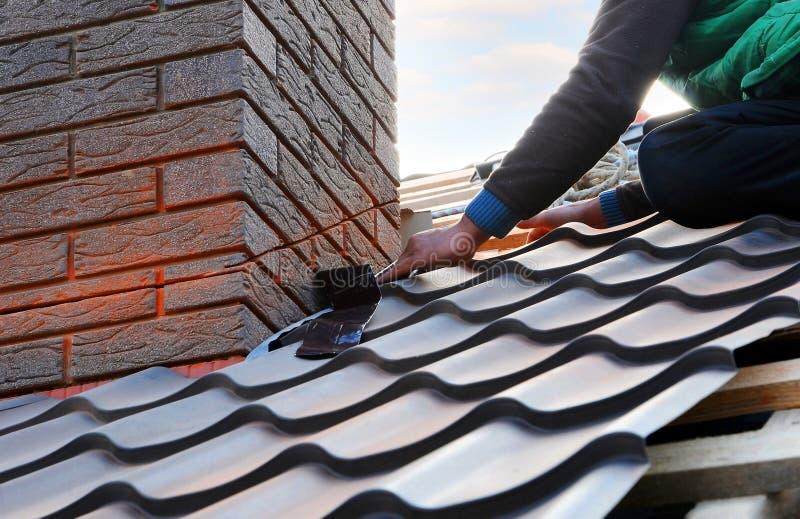 Ο εργαζόμενος οικοδόμων Roofer συνδέει το φύλλο μετάλλων με την καπνοδόχο Ατελής κατασκευή στεγών στοκ εικόνα με δικαίωμα ελεύθερης χρήσης
