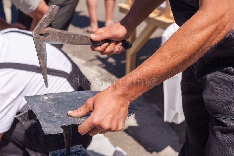 Ο εργαζόμενος παράγει την πλάκα υλικού κατασκευής σκεπής χρησιμοποιώντας ένα σφυρί πλακών στοκ εικόνες
