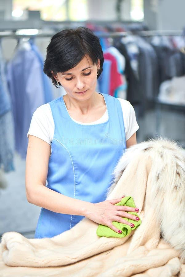 Ο εργαζόμενος πλυντηρίων κοριτσιών σκουπίζει το παλτό με ένα ύφασμα στοκ εικόνες με δικαίωμα ελεύθερης χρήσης