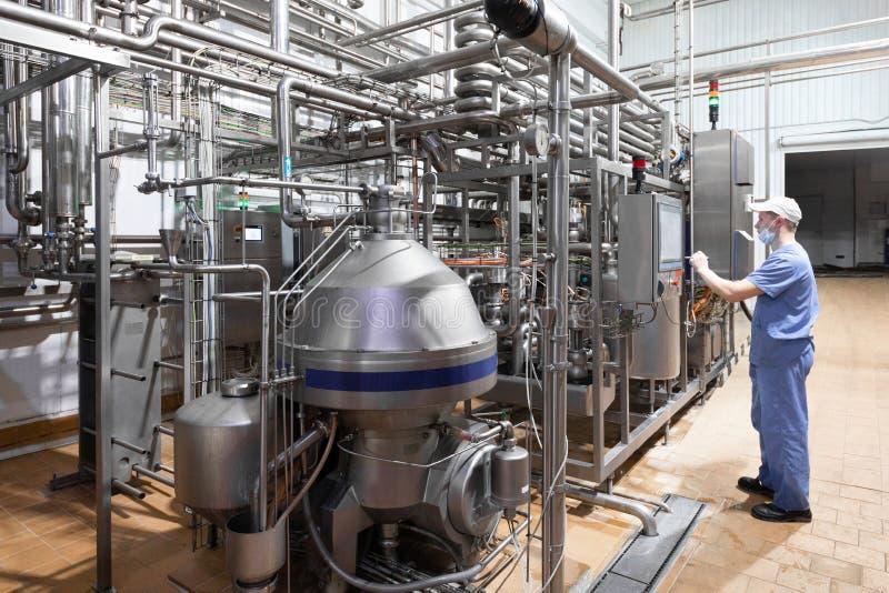 Ο εργαζόμενος σε μια μπλε τήβεννο και μια ΚΑΠ επιθεωρούν το τμήμα παραγωγής γαλακτοκομικού εργοστασίου στοκ φωτογραφίες με δικαίωμα ελεύθερης χρήσης