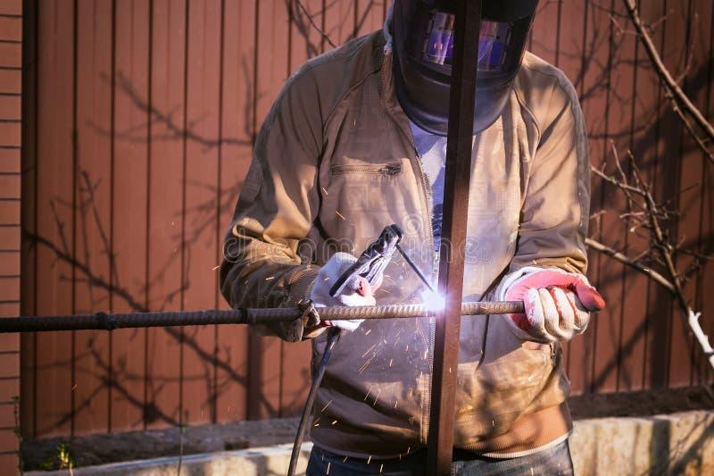 Ο εργαζόμενος στην προστατευτική μάσκα ενώνει στενά το μέταλλο με μια μηχανή συγκόλλησης στοκ φωτογραφία με δικαίωμα ελεύθερης χρήσης