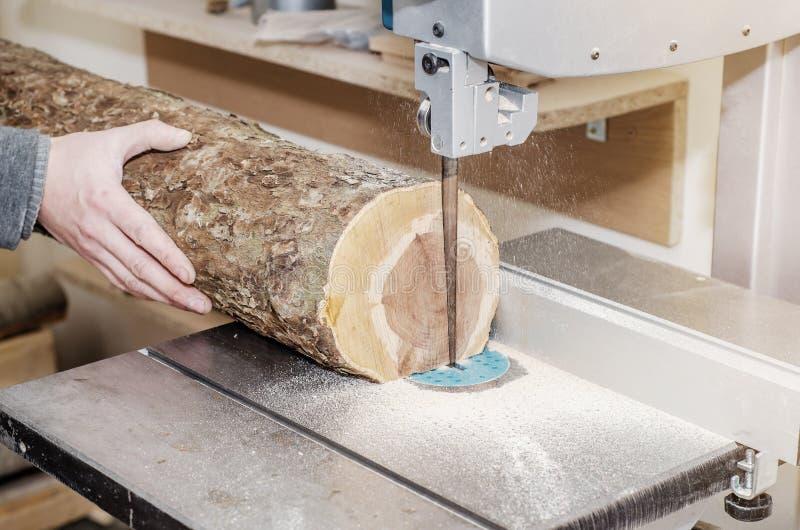 Ο εργαζόμενος στο εργαστήριο ξυλουργικής κόβει το κούτσουρο στους πίνακες χρησιμοποιώντας ένα πριόνι ζωνών joinery Ξύλινες τέχνες στοκ φωτογραφία με δικαίωμα ελεύθερης χρήσης
