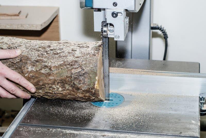 Ο εργαζόμενος στο εργαστήριο ξυλουργικής κόβει το κούτσουρο στους πίνακες χρησιμοποιώντας ένα πριόνι ζωνών joinery Ξύλινες τέχνες στοκ φωτογραφίες με δικαίωμα ελεύθερης χρήσης