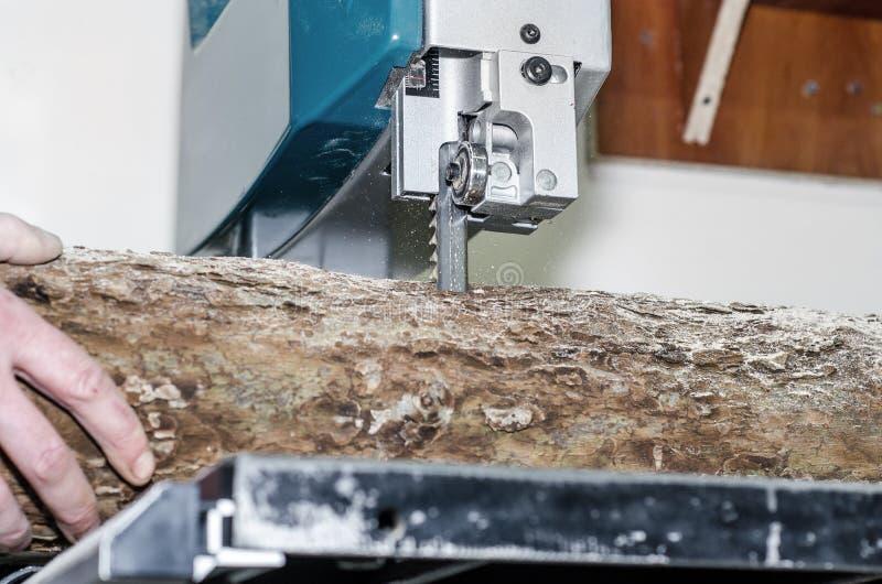 Ο εργαζόμενος στο εργαστήριο ξυλουργικής κόβει το κούτσουρο στους πίνακες χρησιμοποιώντας ένα πριόνι ζωνών joinery Ξύλινες τέχνες στοκ φωτογραφία