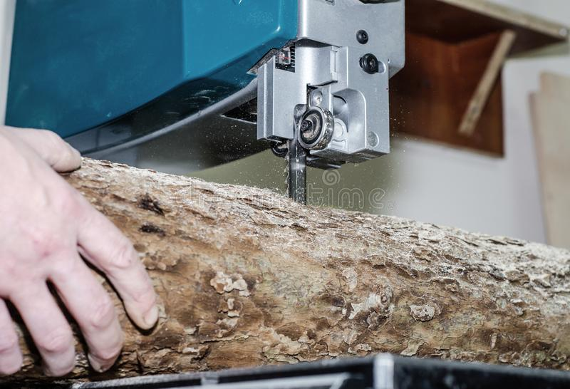 Ο εργαζόμενος στο εργαστήριο ξυλουργικής κόβει το κούτσουρο στους πίνακες χρησιμοποιώντας ένα πριόνι ζωνών joinery Ξύλινες τέχνες στοκ εικόνα με δικαίωμα ελεύθερης χρήσης