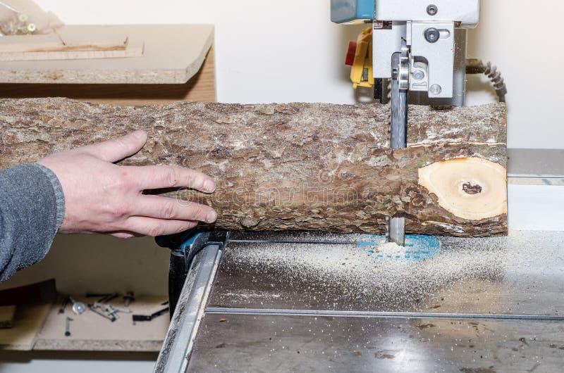 Ο εργαζόμενος στο εργαστήριο ξυλουργικής κόβει το κούτσουρο στους πίνακες χρησιμοποιώντας ένα πριόνι ζωνών joinery Ξύλινες τέχνες στοκ φωτογραφίες