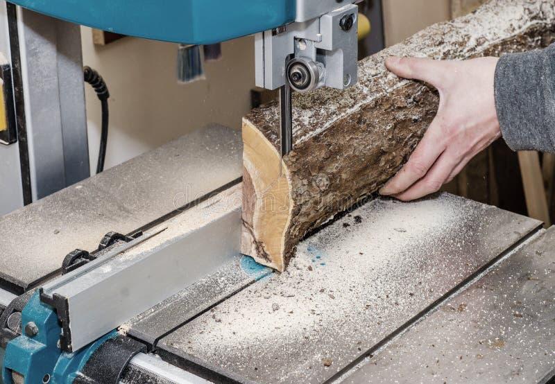 Ο εργαζόμενος στο εργαστήριο ξυλουργικής κόβει το κούτσουρο στους πίνακες χρησιμοποιώντας ένα πριόνι ζωνών joinery Ξύλινες τέχνες στοκ εικόνες με δικαίωμα ελεύθερης χρήσης