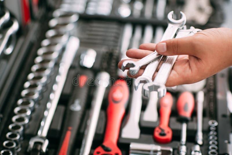 Ο εργαζόμενος στο κατάστημα επιλέγει τα εργαλεία γαλλικών κλειδιών στοκ εικόνα