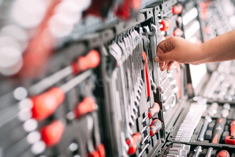 Ο εργαζόμενος στο κατάστημα επιλέγει τα εργαλεία γαλλικών κλειδιών στοκ εικόνα με δικαίωμα ελεύθερης χρήσης