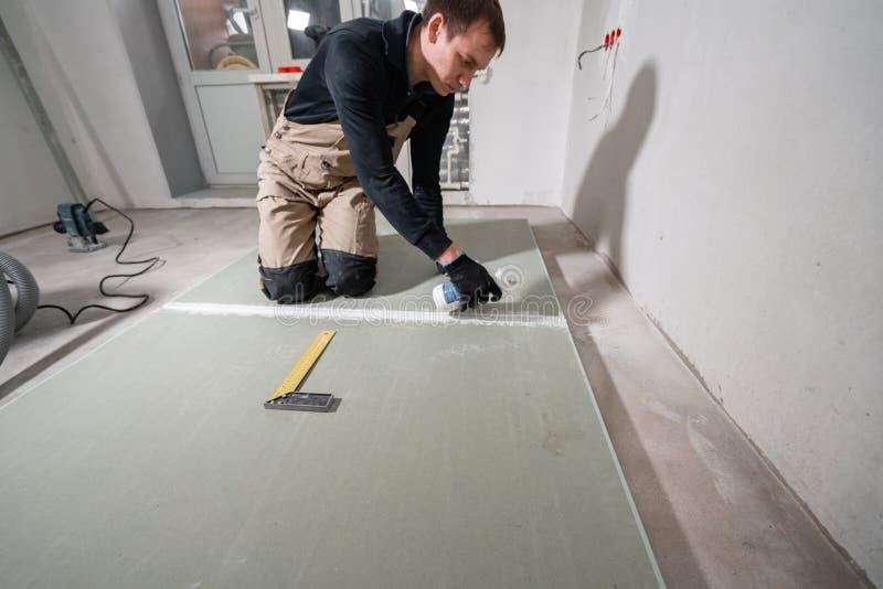 Ο εργαζόμενος χρησιμοποιεί έναν αφρό πολυουρεθάνιου για να κολλήσει τον ξηρό τοίχο σε ενενήντα βαθμούς Επεκτειμένος κόλλα αφρού π στοκ εικόνες
