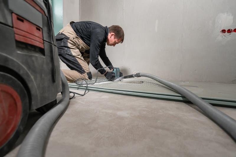 Ο εργαζόμενος χρησιμοποιεί ένα εργαλείο οικοδόμησης, τα εργαλεία άλεσης και μια ηλεκτρική σκούπα ξηρός τοίχος σε ενενήντα βαθμούς στοκ εικόνα