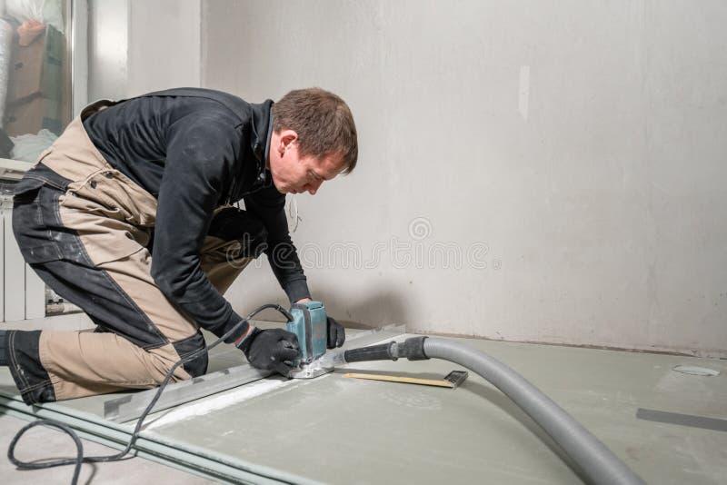 Ο εργαζόμενος χρησιμοποιεί ένα εργαλείο οικοδόμησης, τα εργαλεία άλεσης και μια ηλεκτρική σκούπα ξηρός τοίχος σε ενενήντα βαθμούς στοκ εικόνες