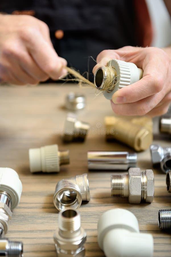Ο εργαζόμενος χρησιμοποιεί τις ίνες κάνναβης ενός υδραυλικού στοκ εικόνες με δικαίωμα ελεύθερης χρήσης