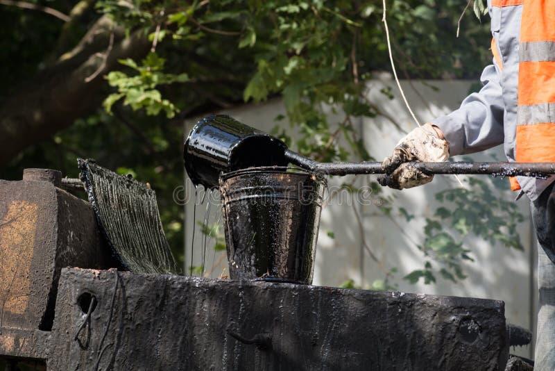 Ο εργαζόμενος χύνει την καυτή πίσσα στον κάδο στοκ φωτογραφίες