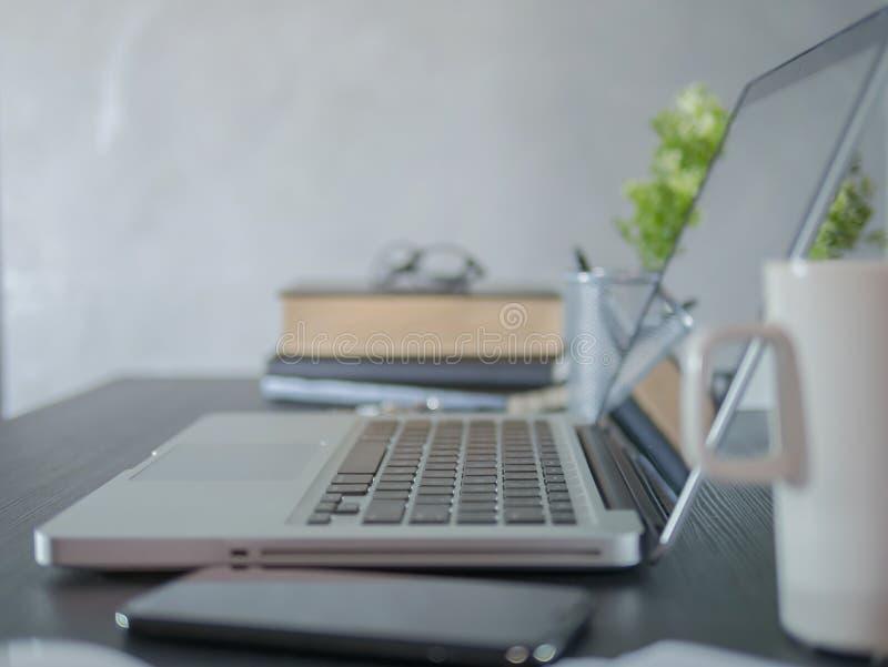 Ο εργασιακός χώρος με το lap-top, smartphone, βιβλίο, γυαλιά στην εργασία παρουσιάζει στο σύγχρονο γραφείο στοκ φωτογραφία