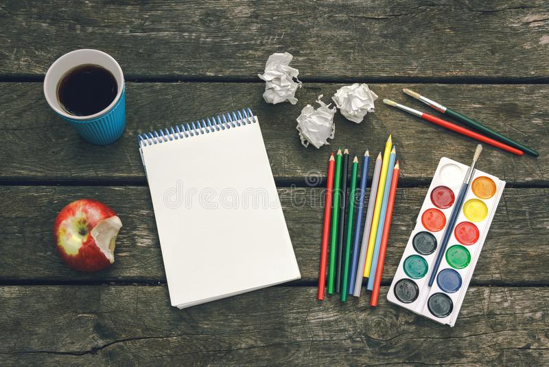 Ο εργασιακός χώρος του καλλιτέχνη δεν σταματά ποτέ Το φλυτζάνι του καυτού καφέ, σημειωματάριο με το κενό φύλλο του εγγράφου, χρωμ στοκ εικόνες