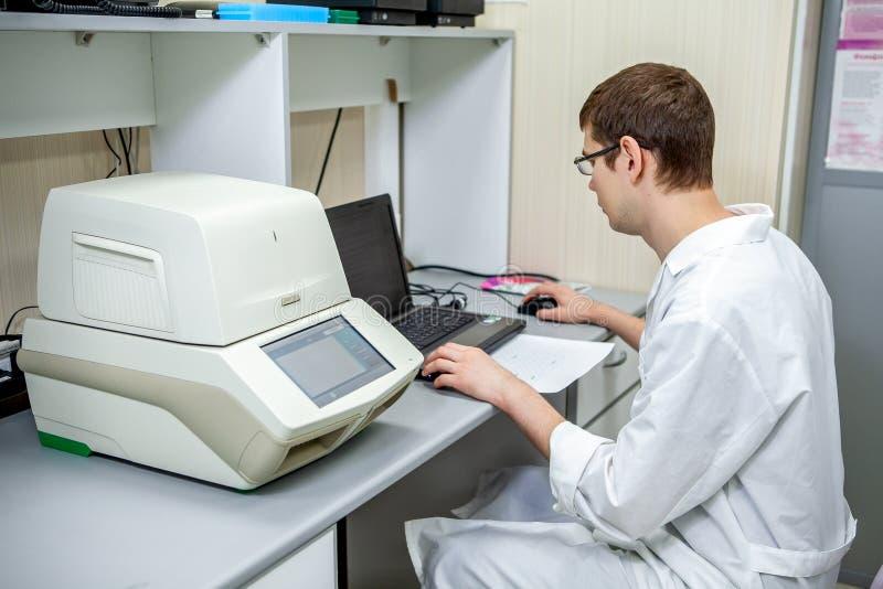 Ο εργαστηριακός ειδικός εξετάζει τα στοιχεία αποκτηθε'ντα σε μια ειδική συσκευή για τα δείγματα σε έναν υπολογιστή στοκ φωτογραφίες με δικαίωμα ελεύθερης χρήσης