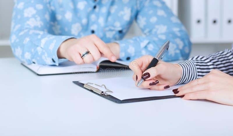 Ο εργοδότης αναγκάζει τον υπάλληλο για να γράψει μια επιστολή της παραίτησης Ακριβώς παραδίδει τον πίνακα στοκ φωτογραφία