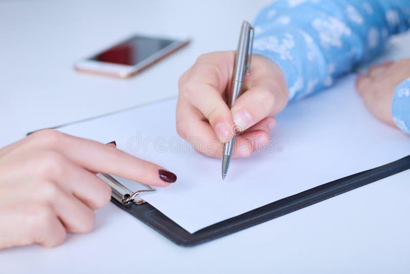 Ο εργοδότης αναγκάζει τον υπάλληλο για να γράψει μια επιστολή της παραίτησης Ακριβώς παραδίδει τον πίνακα στοκ εικόνες