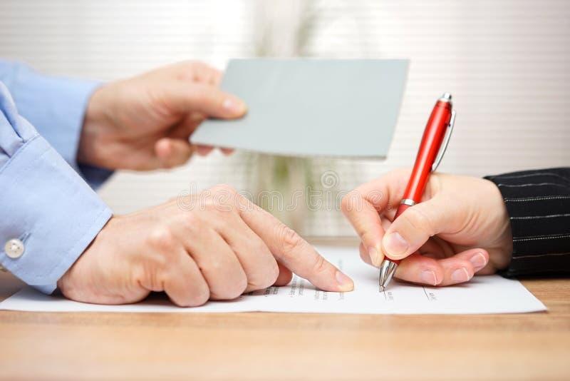 Ο εργοδότης παρουσιάζει υπάλληλο πού να υπογράψει και δίνοντας το βιβλιάριό της στοκ φωτογραφίες