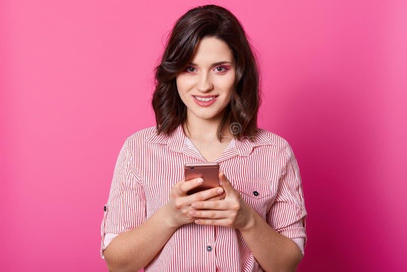 Ο εσωτερικός πυροβολισμός της γοητείας ντυμένο το θηλυκό μοντέρνο πουκάμισο, κρατώντας το smartphone και στα χέρια και εξετάζοντα στοκ εικόνα