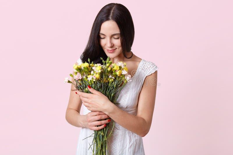 Ο εσωτερικός πυροβολισμός της γυναίκας brunette εξετάζει ήπια τα λουλούδια στα χέρια της, που ντύνονται στο άσπρο φόρεμα, έχει το στοκ εικόνες με δικαίωμα ελεύθερης χρήσης