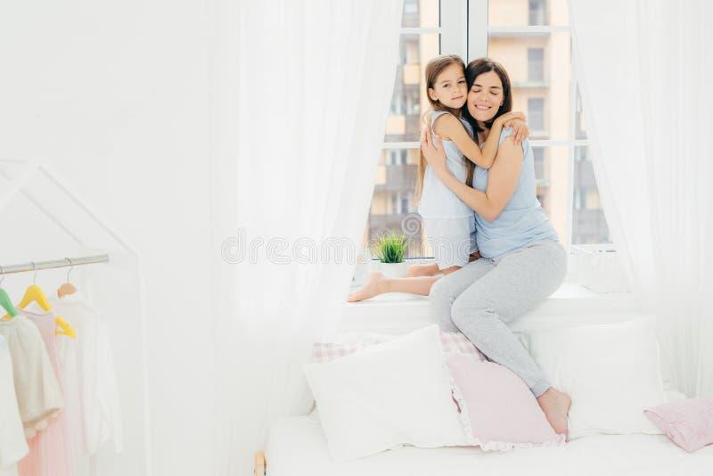 Ο εσωτερικός πυροβολισμός της ευχάριστης κοιτάζοντας θηλυκής μητέρας αγκαλιάζει το μικρό παιδί της, κάθεται στη στρωματοειδή φλέβ στοκ εικόνες
