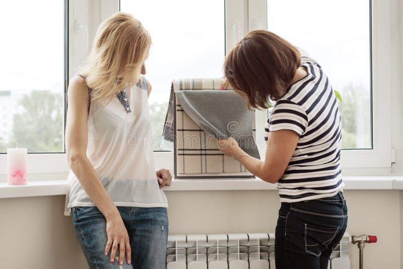 Ο εσωτερικός σχεδιαστής παρουσιάζει δείγματα των υφασμάτων και των εξαρτημάτων για τις κουρτίνες στο καινούργιο σπίτι στοκ φωτογραφία