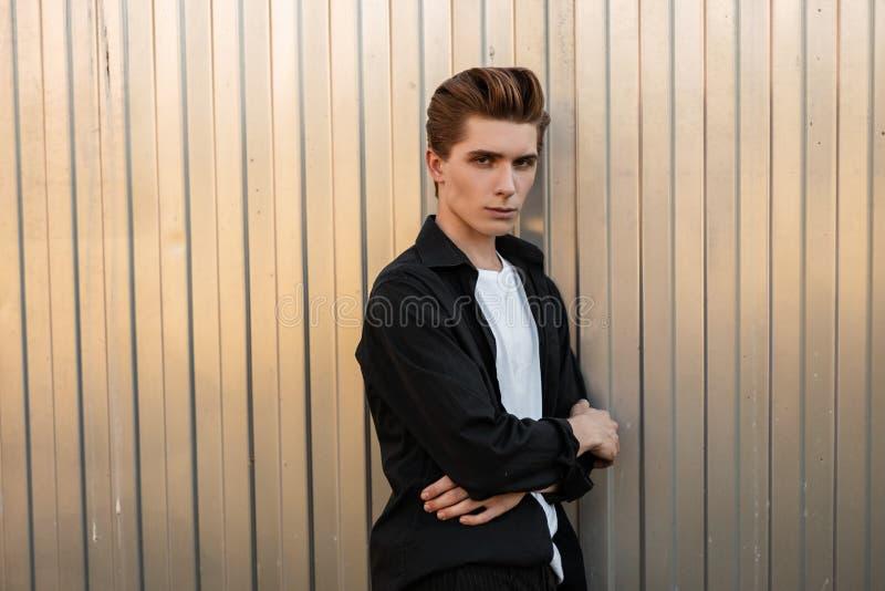 Ο ευρωπαϊκός ελκυστικός νεαρός άνδρας σε ένα μοντέρνο μαύρο πουκάμισο σε μια άσπρη εκλεκτής ποιότητας μπλούζα με ένα μοντέρνο hai στοκ εικόνες