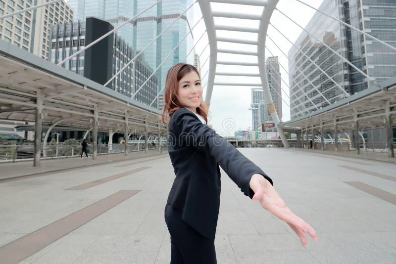 Ο ευρύς πυροβολισμός γωνίας της εύθυμης ασιατικής επιχειρηματία επεκτείνει το χέρι στη κάμερα στο αστικό υπόβαθρο πόλεων Επιχειρη στοκ εικόνα