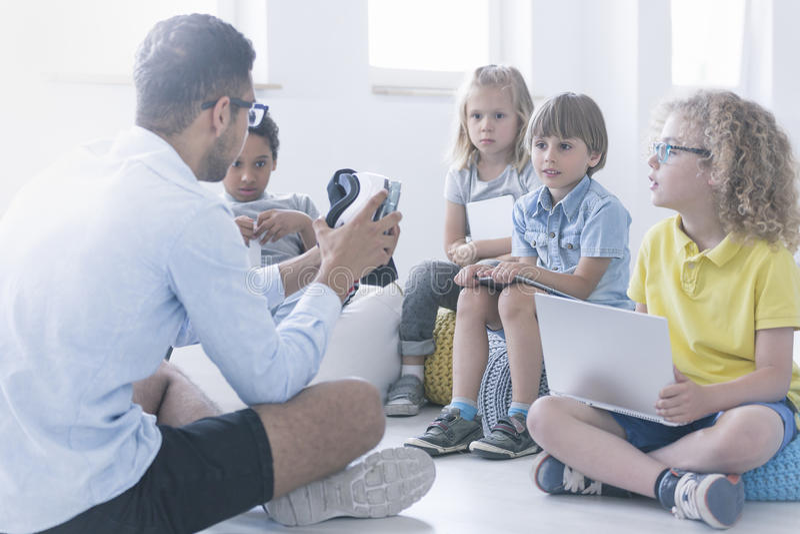 Ο ευτυχής δάσκαλος παρουσιάζει στα παιδιά το ρομπότ στοκ φωτογραφία
