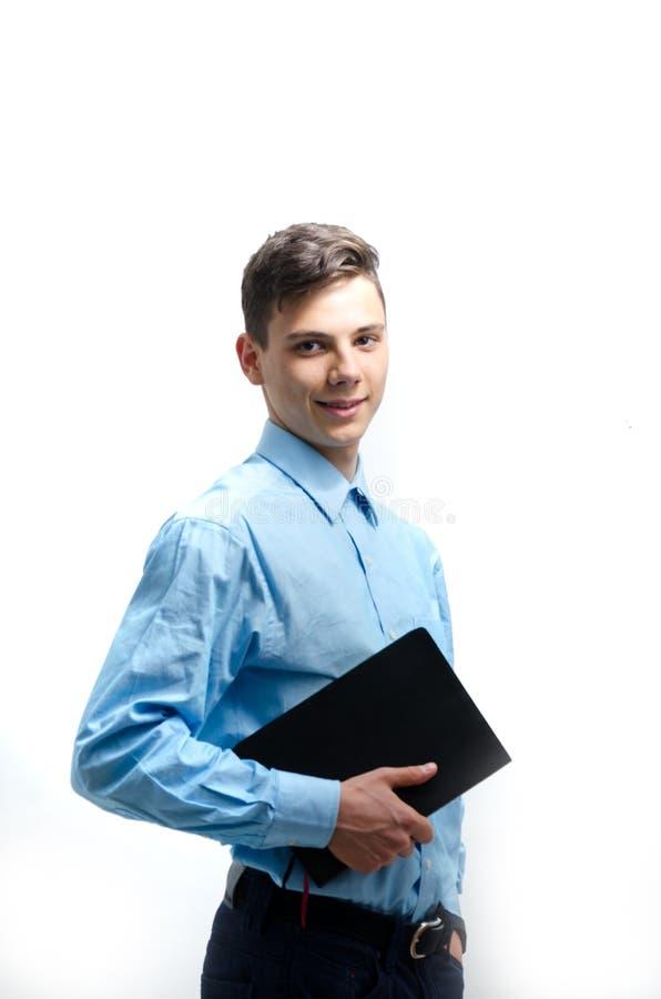 Ο ευτυχής έφηβος κρατά ένα μεγάλο βιβλίο απομονωμένο στο άσπρο υπόβαθρο στοκ φωτογραφίες με δικαίωμα ελεύθερης χρήσης
