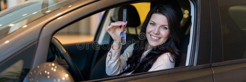 Ο ευτυχής αγοραστής γυναικών εξετάζει το νέο όχημά της στη εμπορία αυτοκινήτων στοκ εικόνα με δικαίωμα ελεύθερης χρήσης