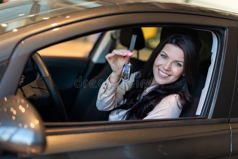 Ο ευτυχής αγοραστής γυναικών εξετάζει το νέο όχημά της στη εμπορία αυτοκινήτων στοκ εικόνα