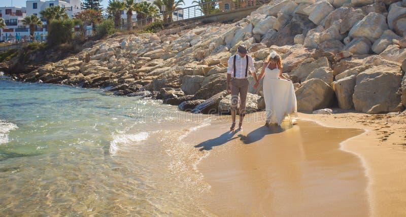 Ο ευτυχής ακριβώς παντρεμένος νέος εορτασμός γαμήλιων ζευγών και έχει τη διασκέδαση στην όμορφη παραλία στοκ φωτογραφία με δικαίωμα ελεύθερης χρήσης