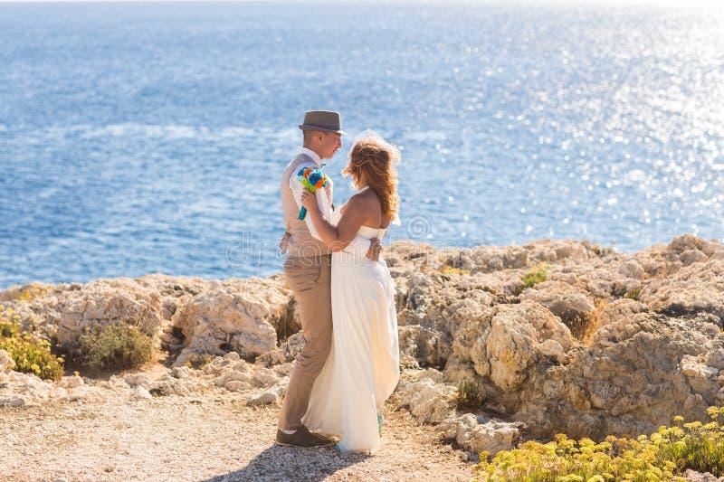 Ο ευτυχής ακριβώς παντρεμένος νέος εορτασμός γαμήλιων ζευγών και έχει τη διασκέδαση στην όμορφη παραλία στοκ φωτογραφία