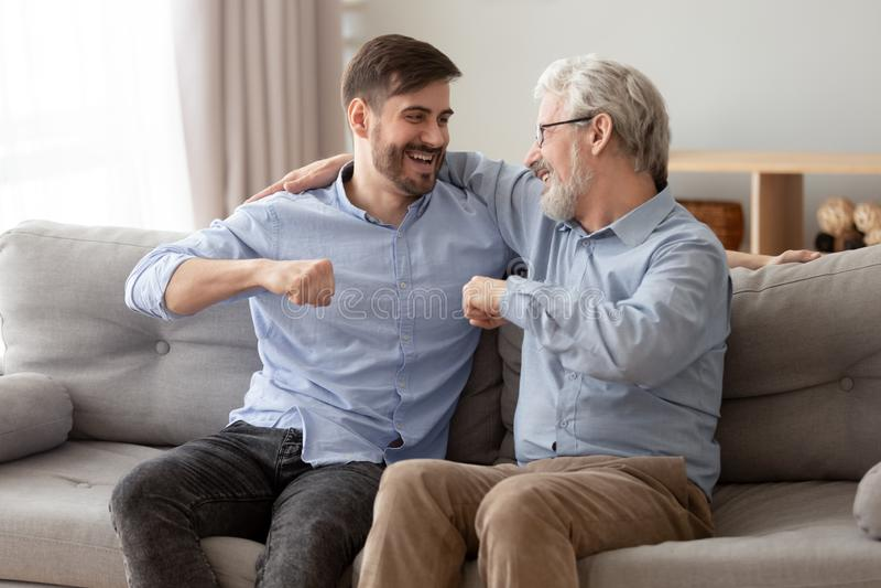 Ο ευτυχής αυξημένος γιος και ο ανώτερος μπαμπάς χαλαρώνουν στο σπίτι από κοινού στοκ εικόνες