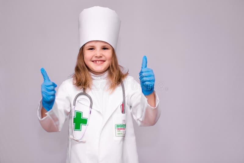 Ο ευτυχής γιατρός μικρών κοριτσιών ιατρικό σε ομοιόμορφο παρουσιάζει αντίχειρα στοκ εικόνα με δικαίωμα ελεύθερης χρήσης