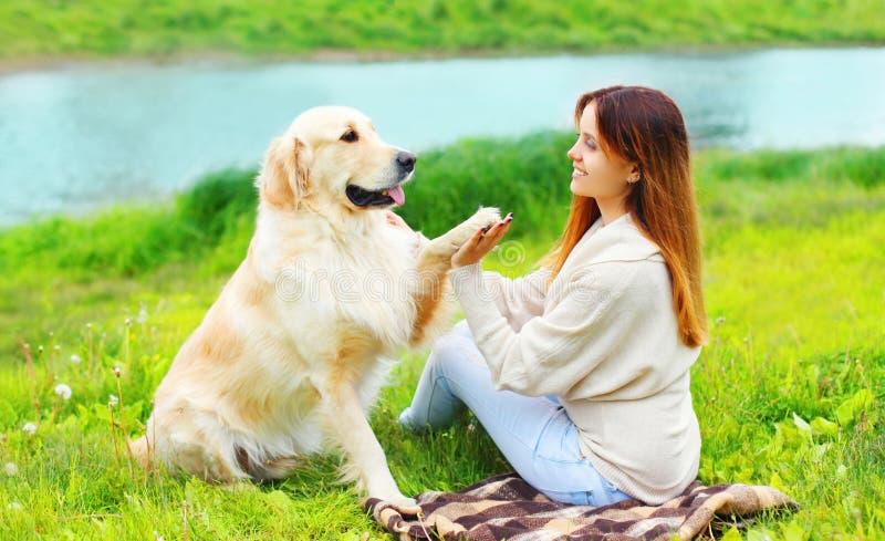 Ο ευτυχής ιδιοκτήτης γυναικών εκπαιδεύει το χρυσό Retriever της σκυλί στη χλόη και δίνει το πόδι στο χέρι στοκ φωτογραφία