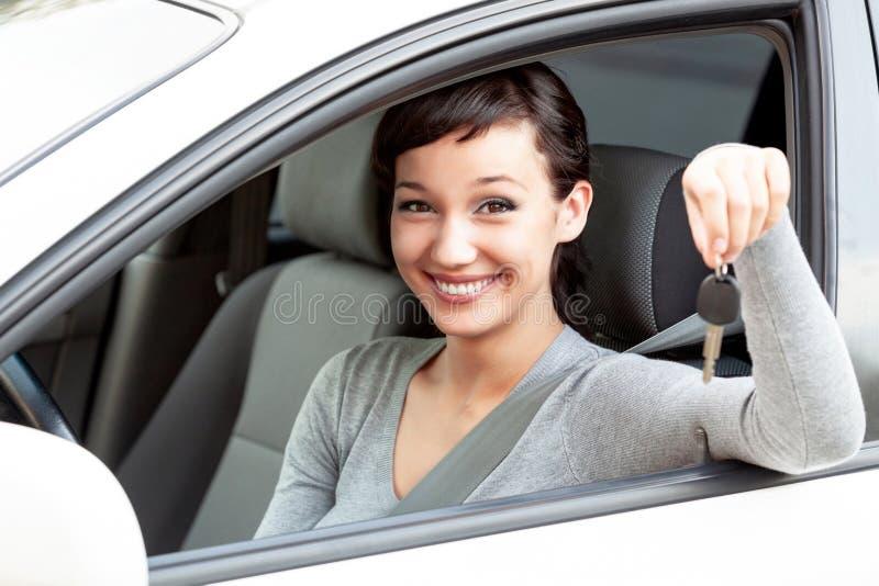 Ο ευτυχής ιδιοκτήτης ενός νέου αυτοκινήτου παρουσιάζει κλειδί αυτοκινήτων στοκ εικόνα