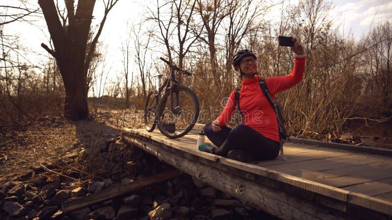 Ο ευτυχής καυκάσιος ποδηλάτης γυναικών κάνει μια φωτογραφία της ένα selfie στο τηλέφωνο καθμένος στη γέφυρα πέρα από έναν ποταμό  στοκ εικόνες