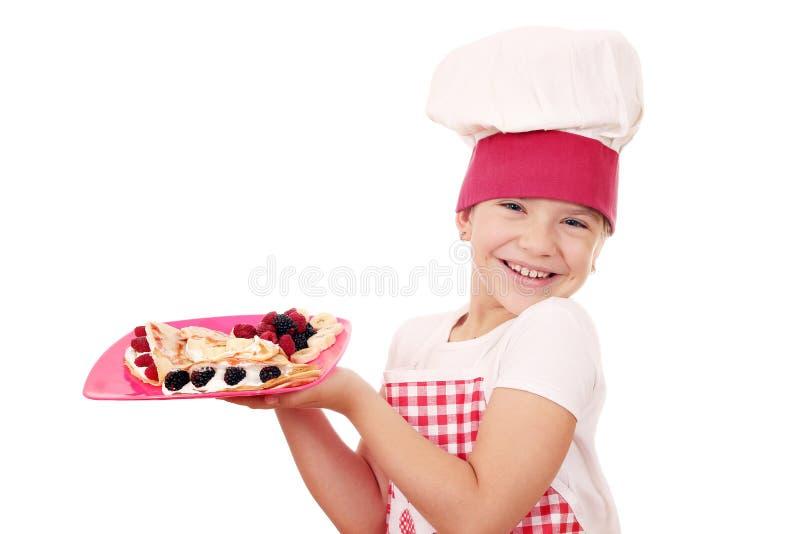 Ο ευτυχής μάγειρας μικρών κοριτσιών με crepes στοκ φωτογραφία με δικαίωμα ελεύθερης χρήσης
