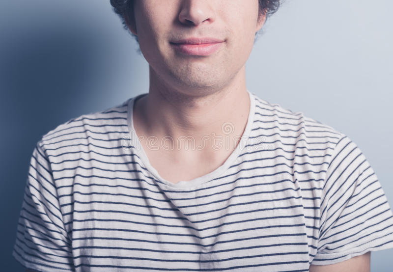 Ο ευτυχής νεαρός άνδρας είναι μπλούζα stripey στοκ φωτογραφία