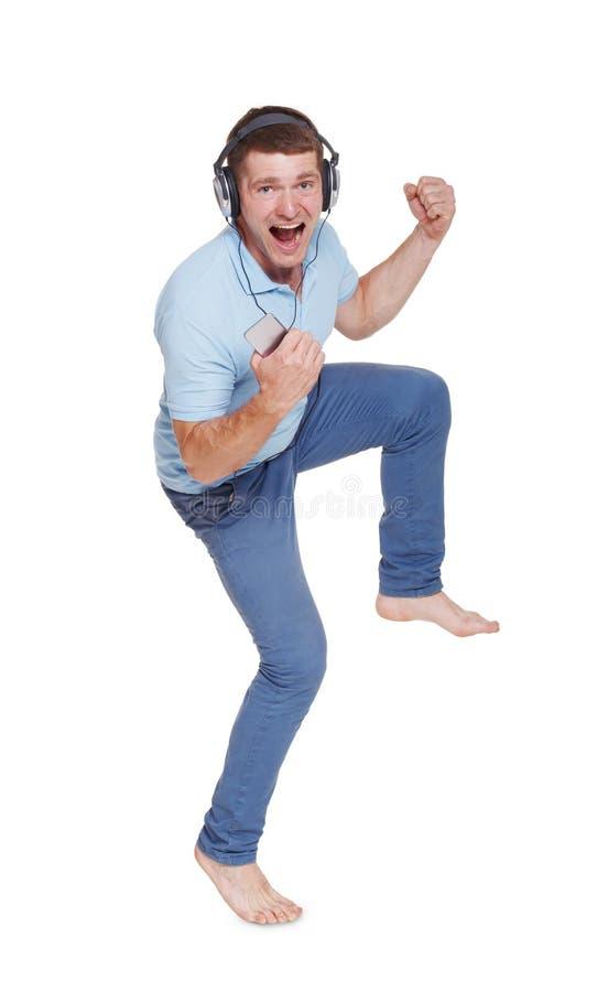 Ο ευτυχής νεαρός άνδρας με τα ακουστικά τραγουδά, χορεύει, απολαμβάνει τη μουσική στοκ φωτογραφία