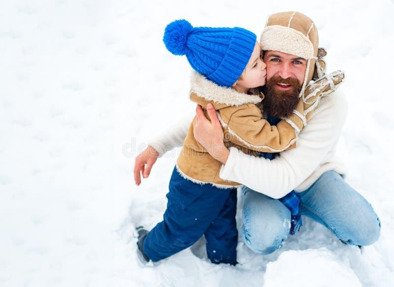 Ο ευτυχής οικογενειακός γιος αγκαλιάζει τον μπαμπά του στις χειμερινές διακοπές r Μπαμπάς και αγόρι που χαμογελούν και που αγκαλι στοκ φωτογραφία