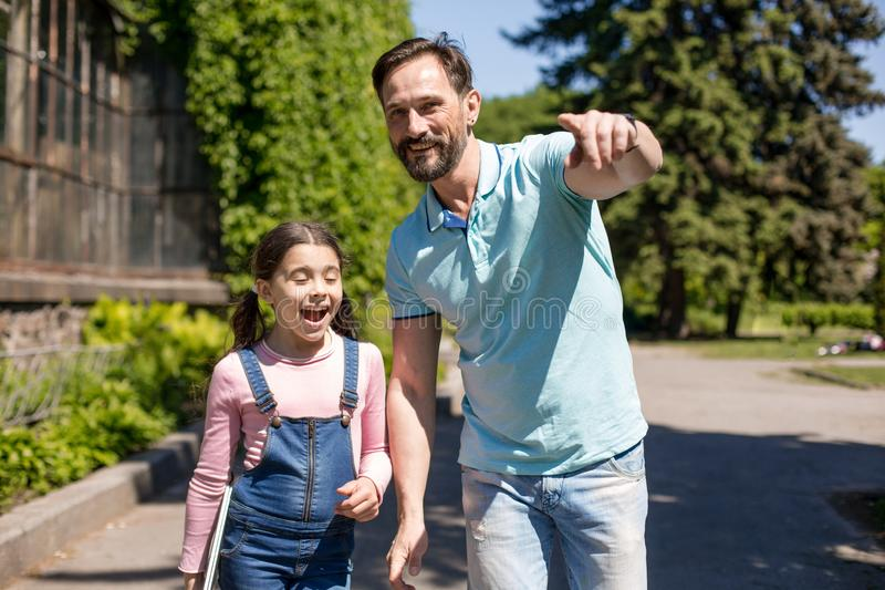 Ο ευτυχής πατέρας και λίγη κόρη περπατούν κατά μήκος του δρόμου στο πάρκο και το χαμόγελο στοκ φωτογραφίες