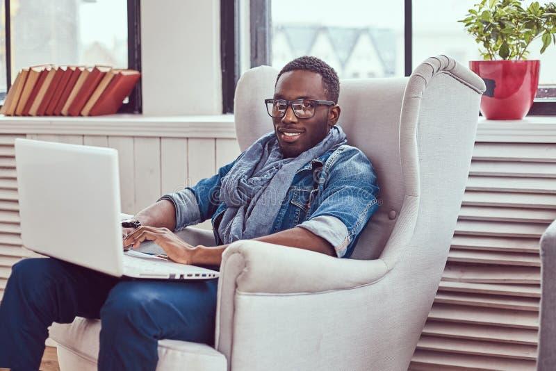Ο ευτυχής σπουδαστής αφροαμερικάνων κάθεται σε μια καρέκλα και χρησιμοποίηση ενός lapto στοκ φωτογραφία