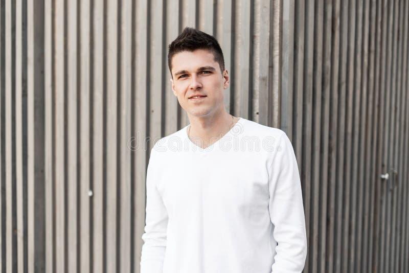 Ο ευτυχής χαριτωμένος νεαρός άνδρας με ένα όμορφο χαμόγελο με ένα μοντέρνο hairstyle σε ένα άσπρο πουκάμισο στέκεται στην πόλη στοκ φωτογραφία με δικαίωμα ελεύθερης χρήσης